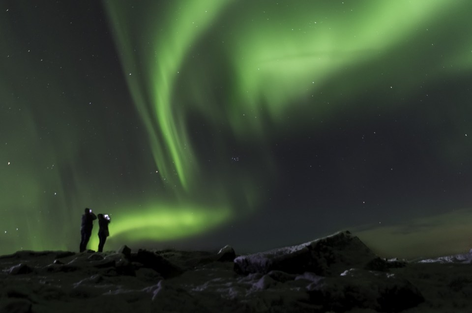 two people watching the northern lights in Iceland