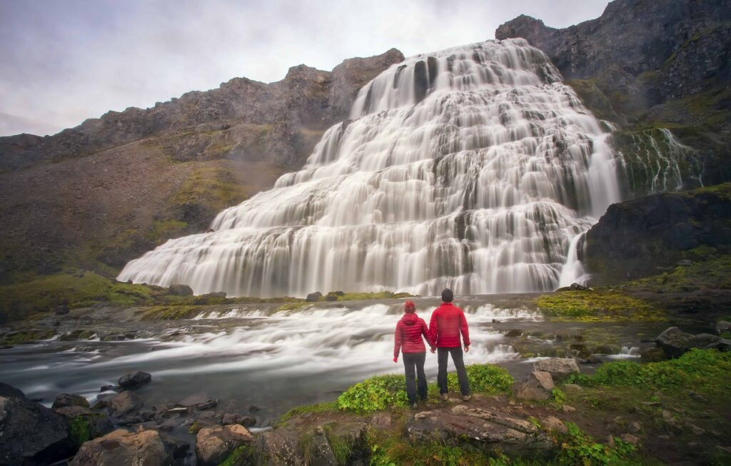 two people standing in front of Dynjandi waterfall in the Westfjords of Iceland