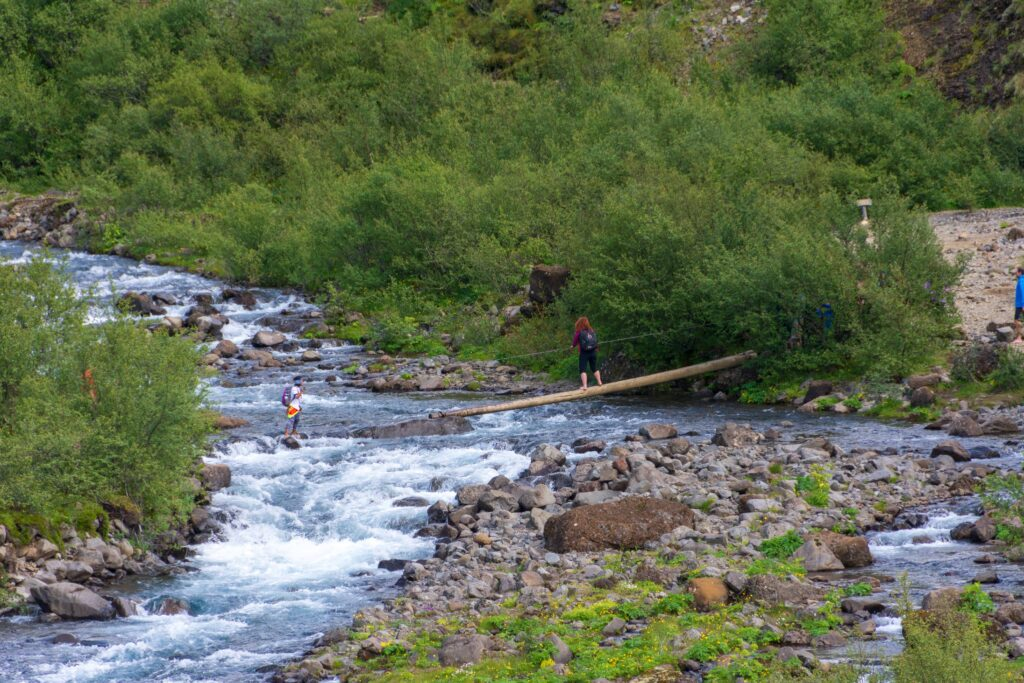 walking over a wooden bridge over a river on the way to Glymur waterfall in west Iceland