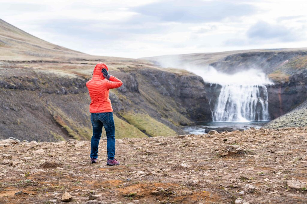 woman standing on top of Þórufoss waterfall in the Golden Circle in Iceland