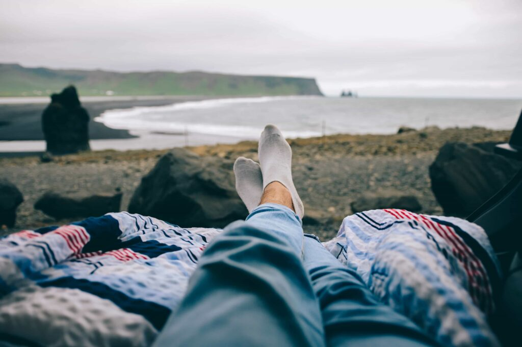 relaxing in the back of a camper van with a view over Reynisfjara black sand beach in South Iceland