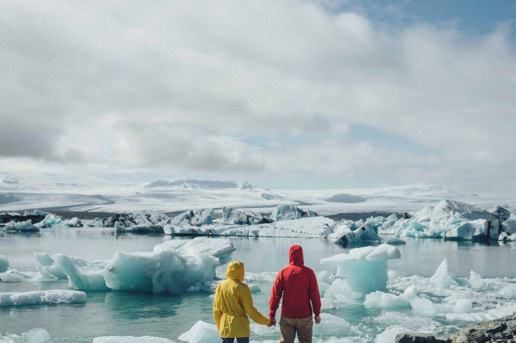 two people standing in front of Jokulsarlon glacier lagoon wearing yellow and red jackets