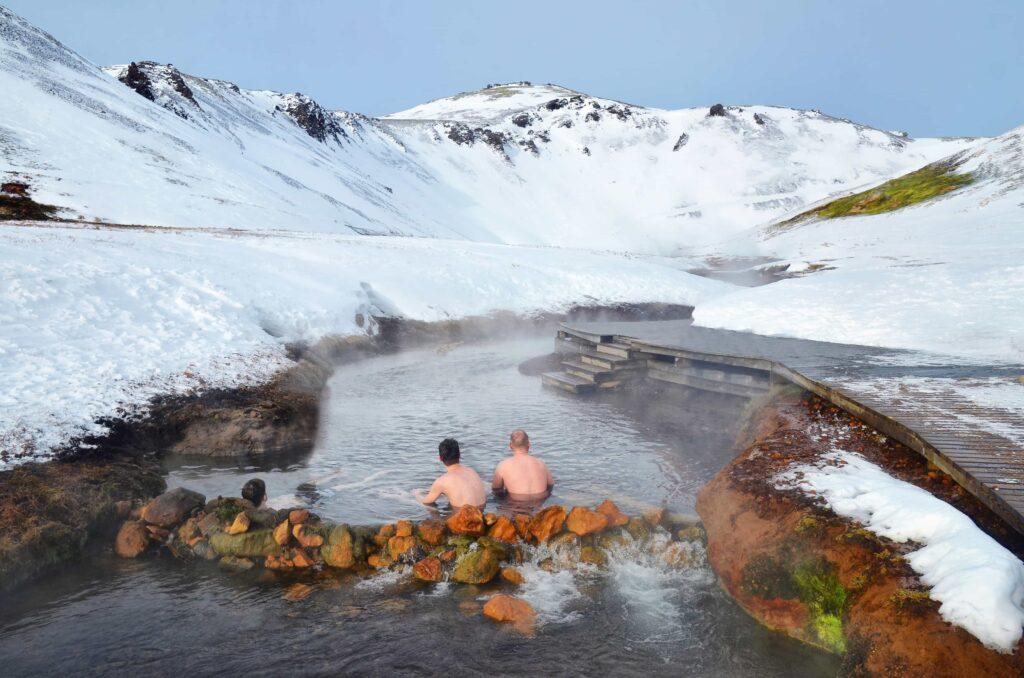 two men sitting in Reykjadalur hot spring on the Reykjadalur hot spring and hike