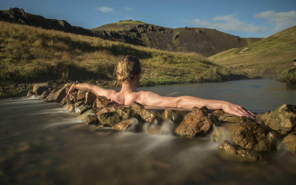 man sitting in Reykjadalur hot spring on the Reykjadalur hot spring and hike
