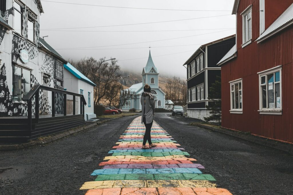 rainbow street and blue church in Seyðisfjordur village in east Iceland