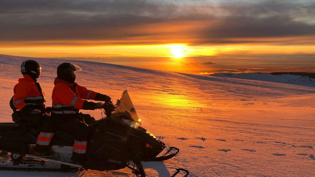 two people watching the sunset on Eyjafjallajokull glacier and volcano snowmobile tour
