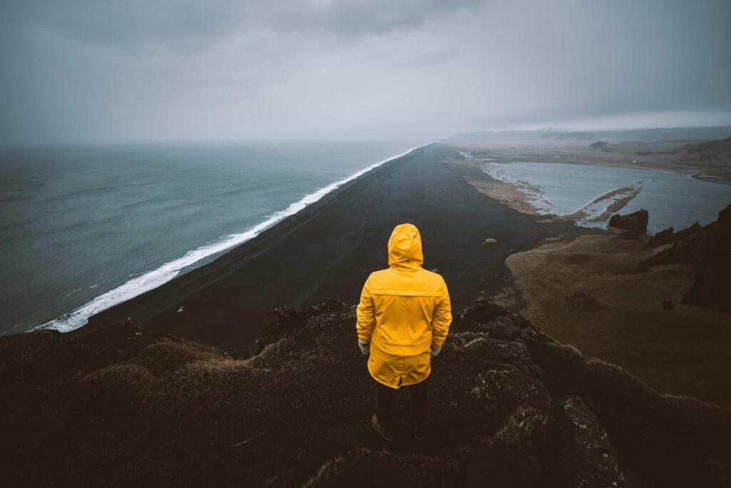 man in yellow raincoat watching over Reynisfjara black sand beach from Reynisfjall mountain