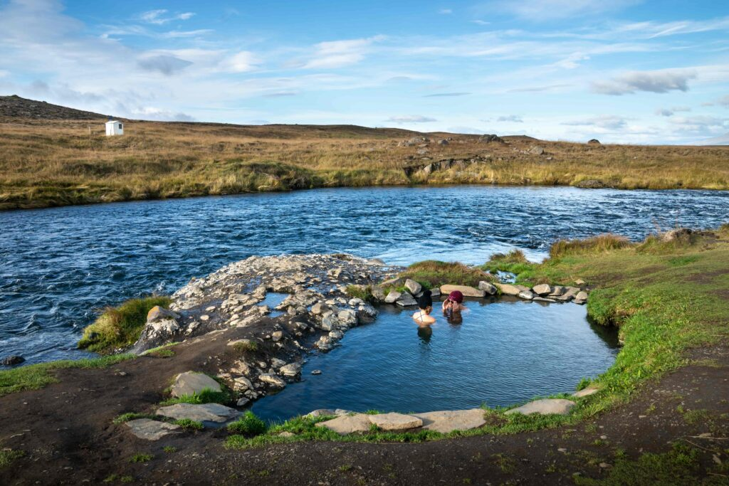 two people bathing in Fosslaug hot spring in north Iceland