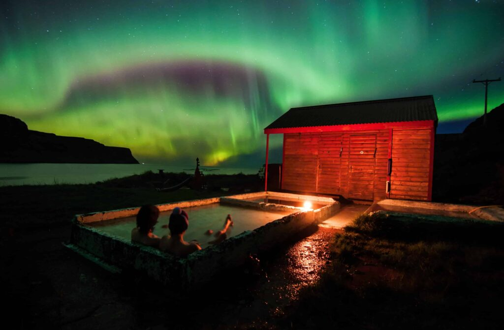Honeymoon in Iceland, watching the northern lights from a hot spring in Iceland