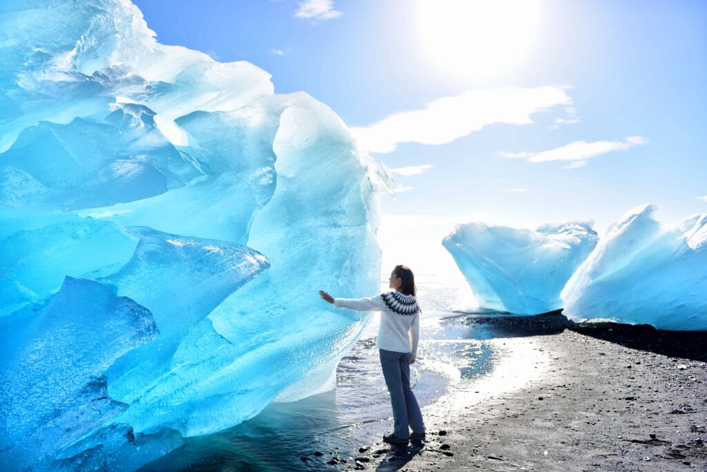 girl standing in front of an ice berg at the Diamond beach in South Iceland