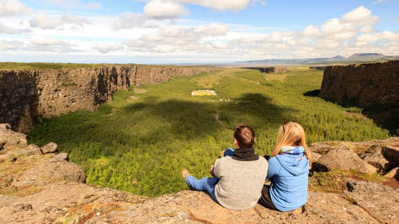two people sitting on top of Ásbyrgi canyon in north Iceland