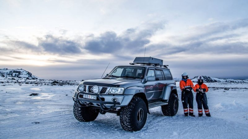 man standing next to a large jeep on Eyjafjallajokull glacier and volcano