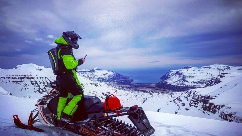 Man on Eyjafjallajokull snowmobile tour with views over south coast of Iceland