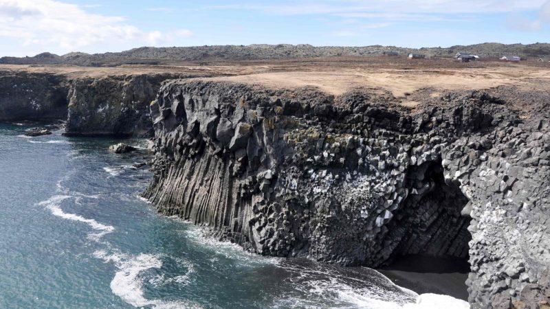 black sand beach and lava cave at Arnarstapi fishing village in snæfellsnes peninsula
