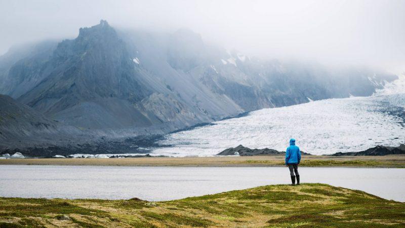 man standing in front of Breiðárlón glacier lagoon and Vatnajokull glacier in south Iceland