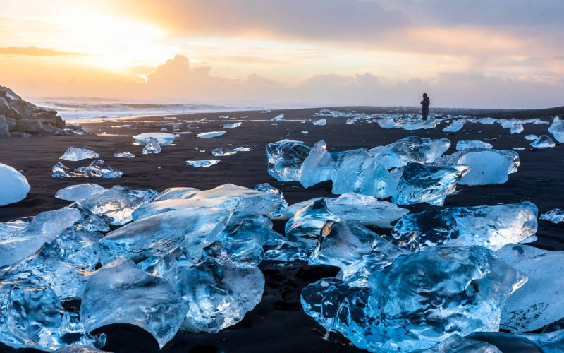 man standing and watching the sunset at Diamond Beach in south Iceland