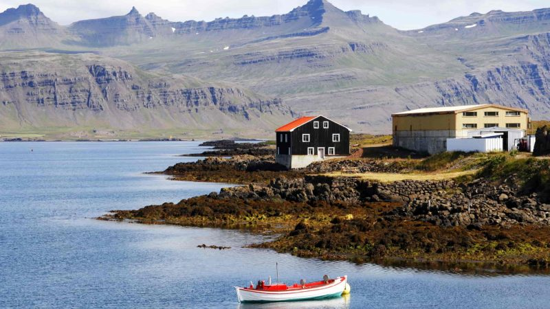 boat and a small house next to the sea in Djupivogur fishing village in east Iceland