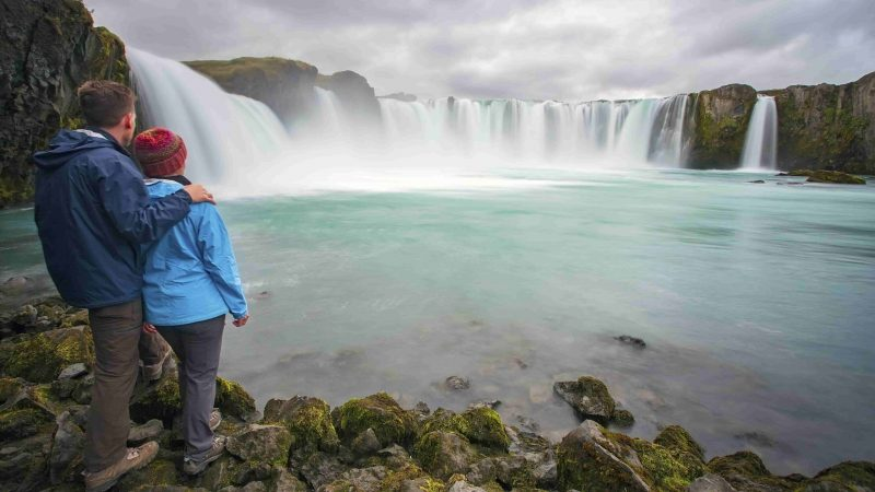 two people standing below Goðafoss waterfall and looking up to it
