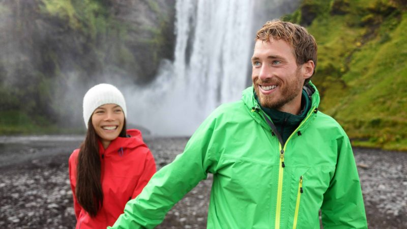 Honeymoon in Iceland, couple in front of Skógafoss waterfall