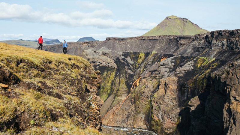 two man standing on top of a canyon watching the views