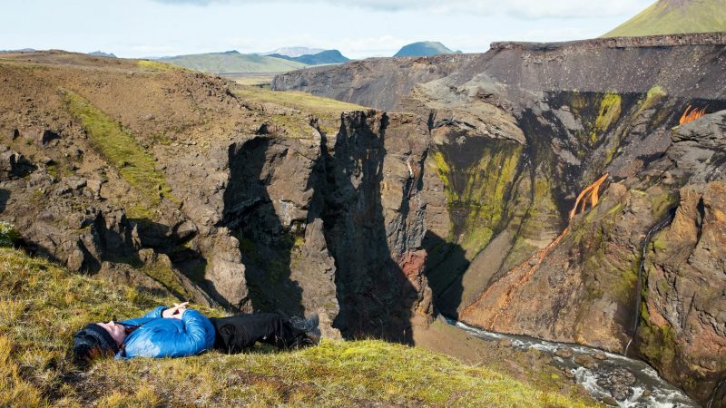 man in blue coat laying in the grass and relaxing in the Icelandic nature