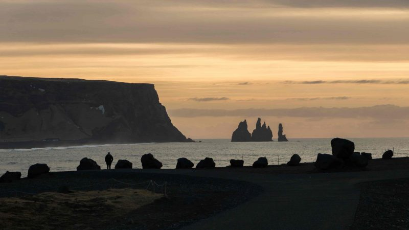 Kirkjufjara black sand beach and Eagle Rock in south Iceland with views over to Reynisfjara and Reynisdrangar