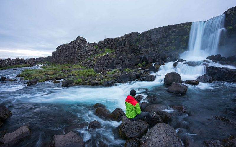 man sitting in front of Öxarárfoss waterfall in Thingvellir National Park in the Golden Circle