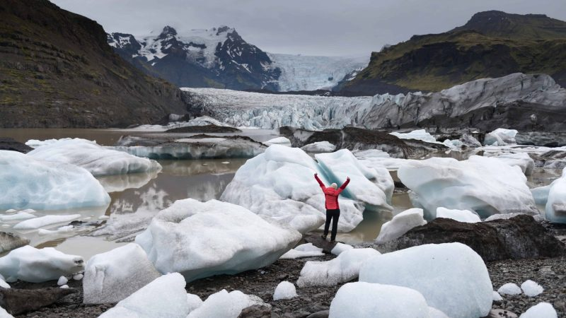 woman in pink coat next to Svínafellsjokull glacier in south Iceland