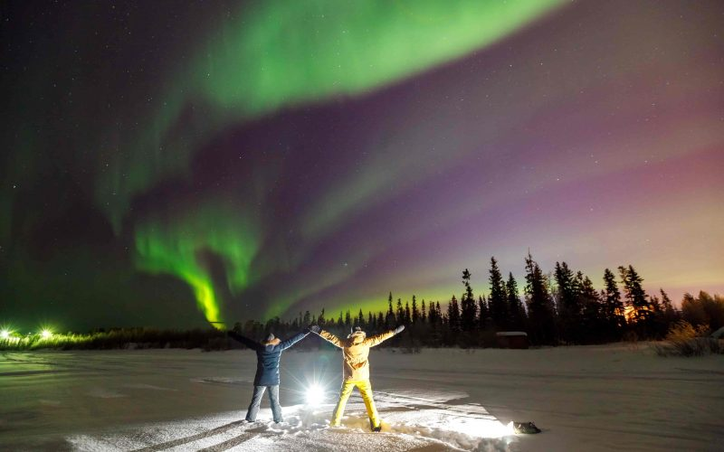 people under the northern lights during winter in Iceland