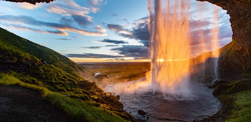 midnight sun seen from behind Seljalandsfoss waterfall in south Iceland