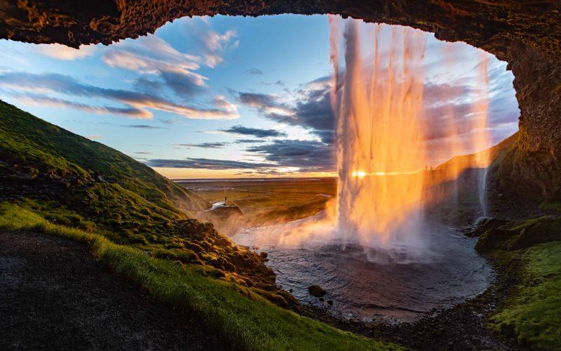 midnight sun seen from behind Seljalandsfoss waterfall in south Iceland