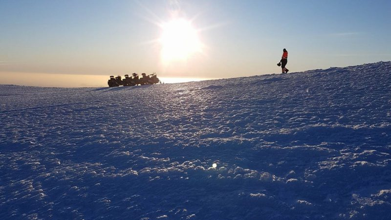 sun shining above Eyjafjallajokull glacier volcano on a snowmobile tour