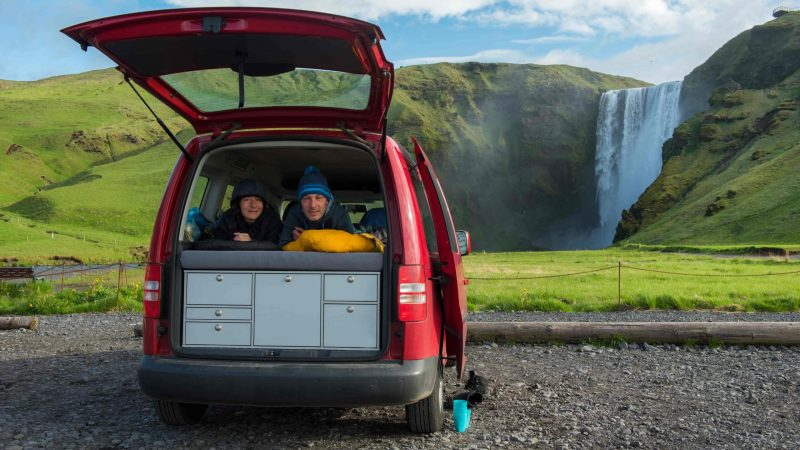 two people in a camper van next to Skógafoss in south Iceland