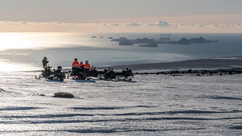 people on Eyjafjallajokull snowmbobile tour with views over Vestmannaeyjar islands in south Iceland