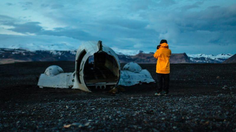 man in yellow raincoat in front of Solheimasandur plane wreck on Solheimasandur black sand beach in south Iceland