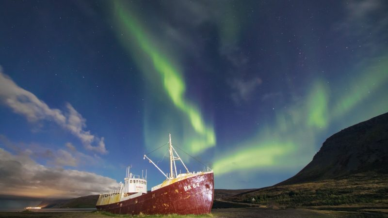 northern lights over Garðar BA 64 Ship wreck in Westfjords