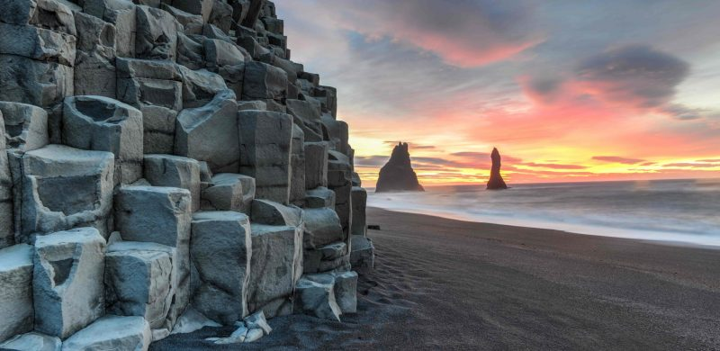 Reynisfjara black sand beach and Reynisdrangar basalt columns at sunset