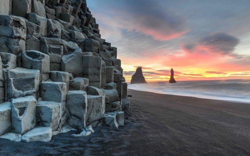 Reynisfjara black sand beach and Reynisdrangar basalt columns at sunset