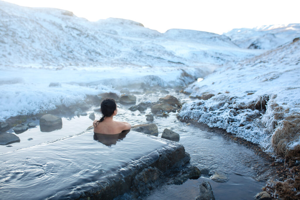 The girl bathes in a hot spring in the open air with a gorgeous view of the snowy mountains. Incredible iceland in winter, Hrunalaug hot spring in the golden circle in Iceland