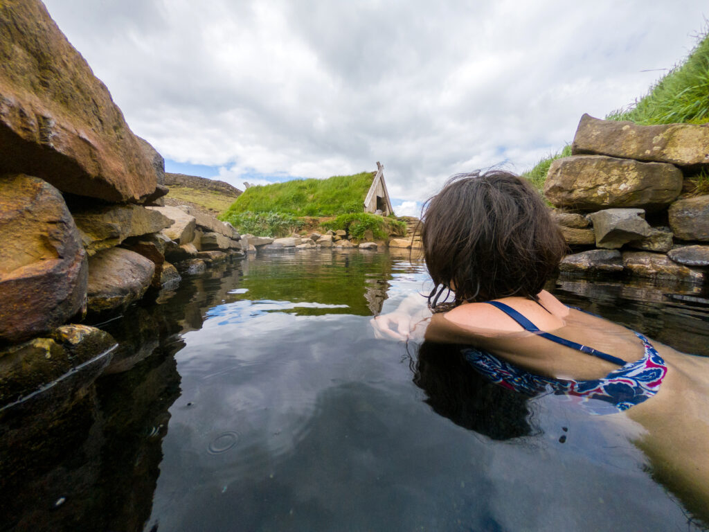 Woman bathing in a small hot pool in Hrunalaug, Iceland