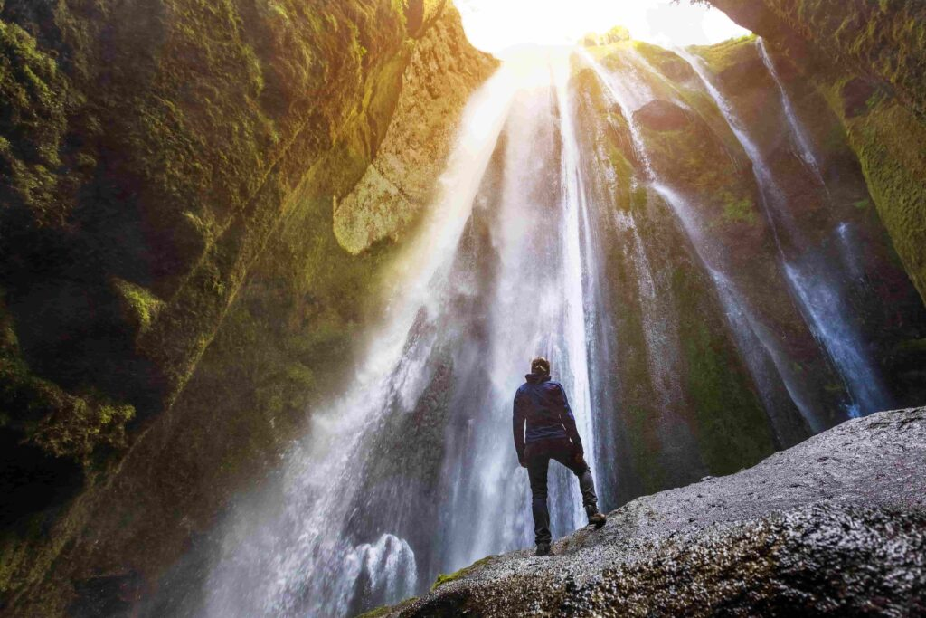 woman standing inside the canyon watching Gljufrabui waterfall in south Iceland