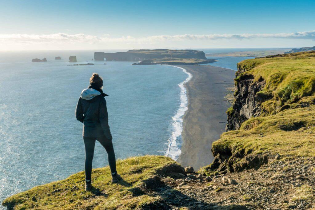 woman standing on top of Reynisfjall watching over Reynisfjara black sand beach and Dyrhólaey