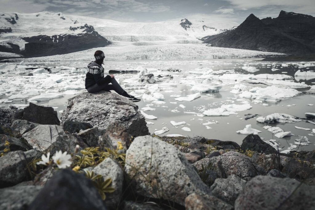 girl sitting on a stone with a view over Fjallsárlón glacier lagoon in south Iceland