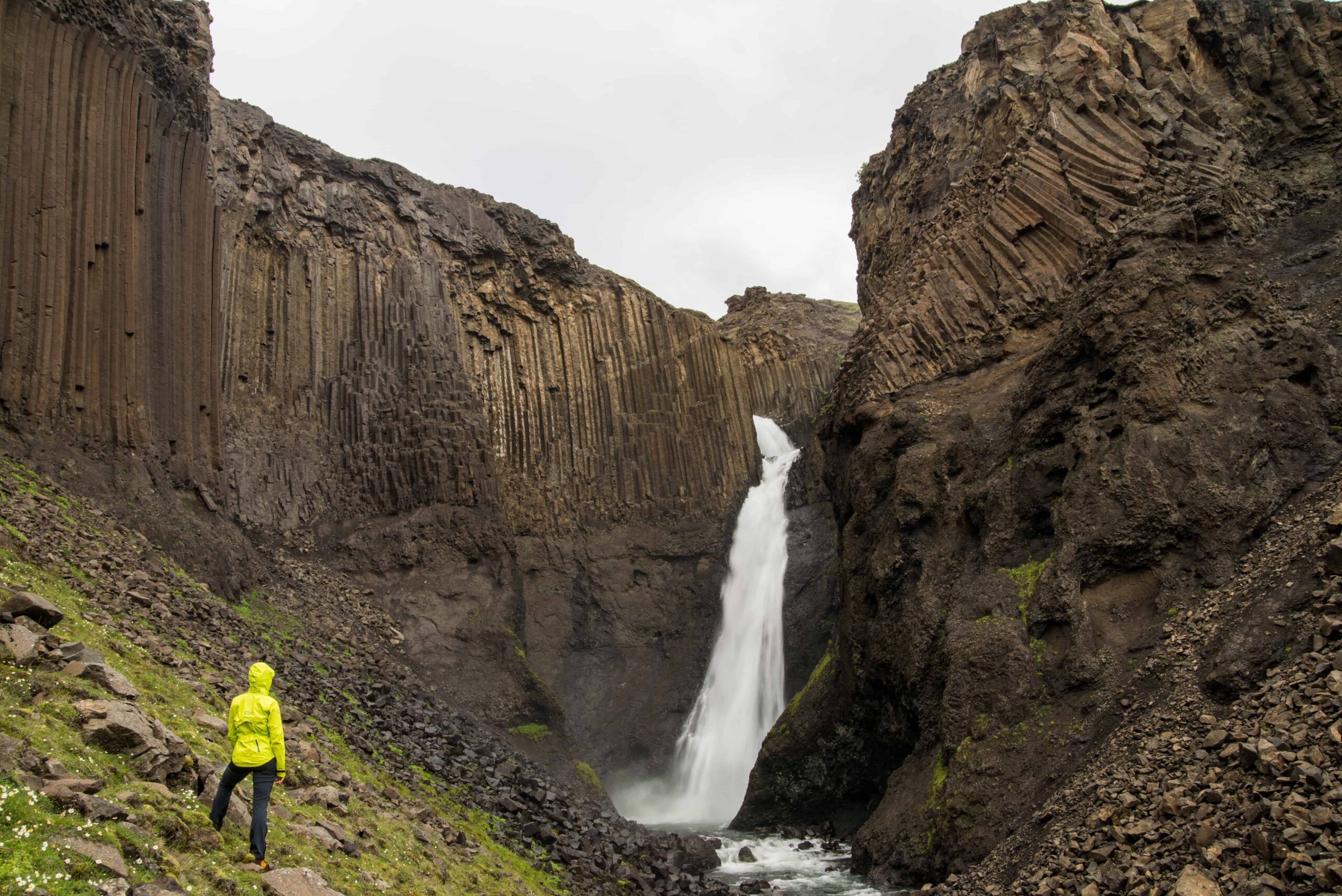 woman in yellow raincoat standing in front of Litlanesfoss basalt column waterfall in East Iceland