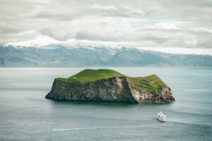 View over the small island and a boat next to Westman Islands in south Iceland