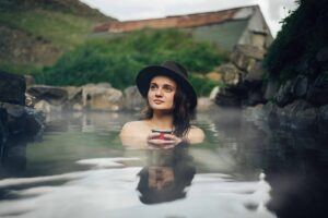 woman sitting in Hrunalaug hot spring in the Golden Circle Iceland