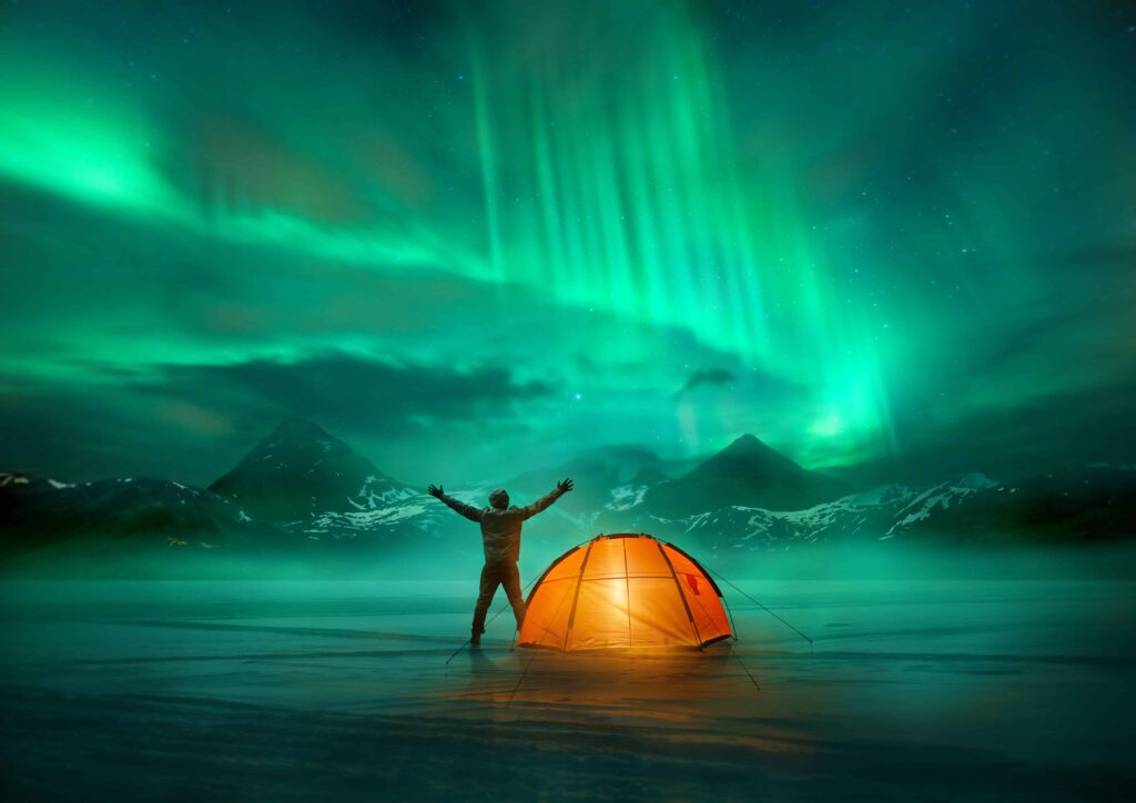 camping under the northern lights in Iceland, man standing with his tent and northern lights in Iceland
