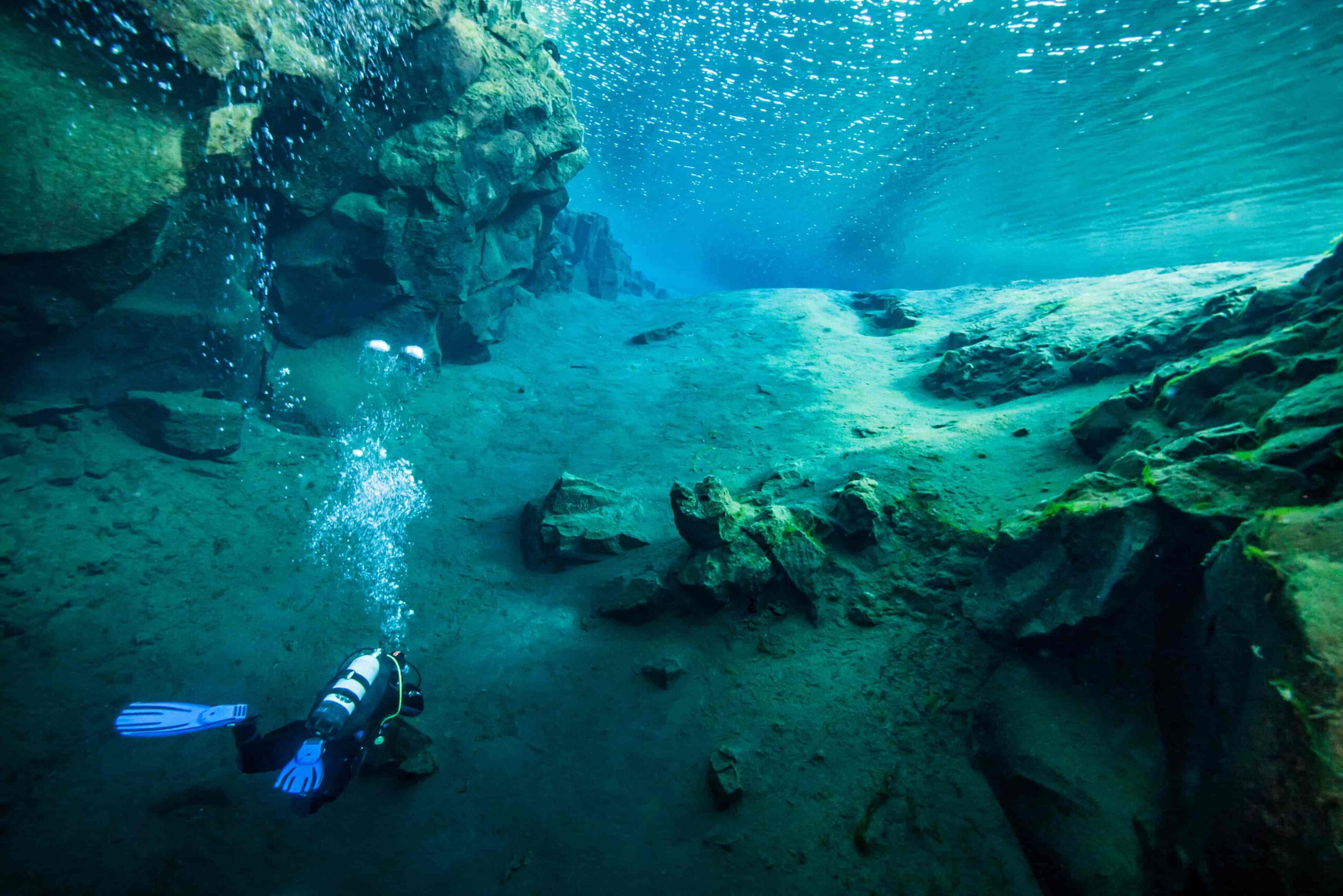 man diving in the clear water in Silfra in Thingvellir National Park in Iceland, man diving between the continents of Europe and North America