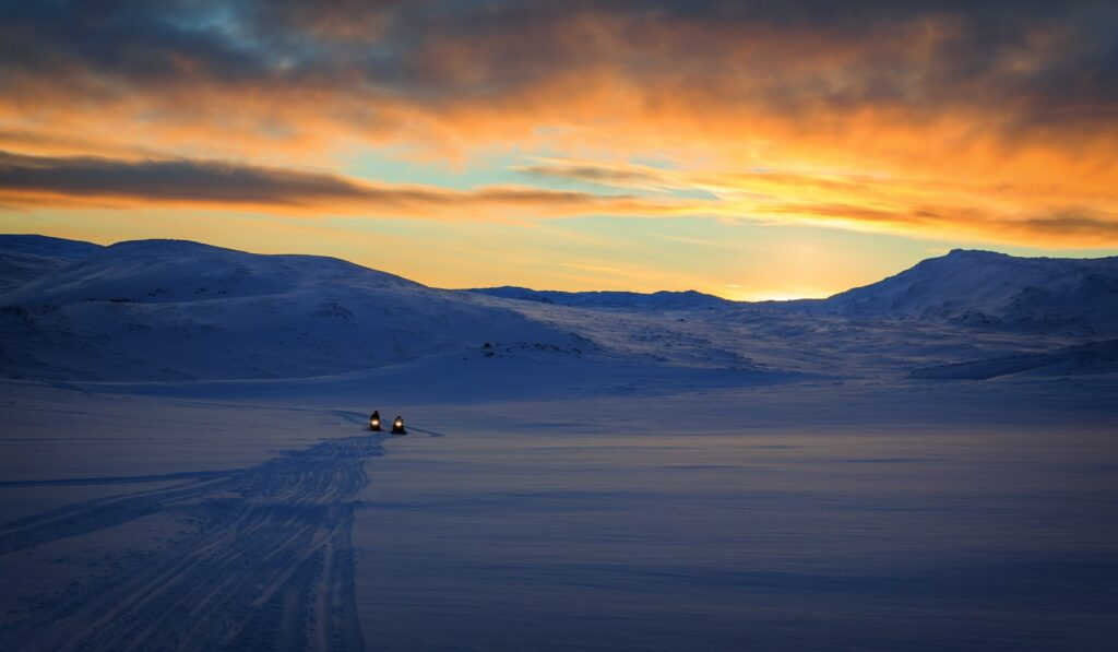 sunset over the glacier on a snowmobile trip