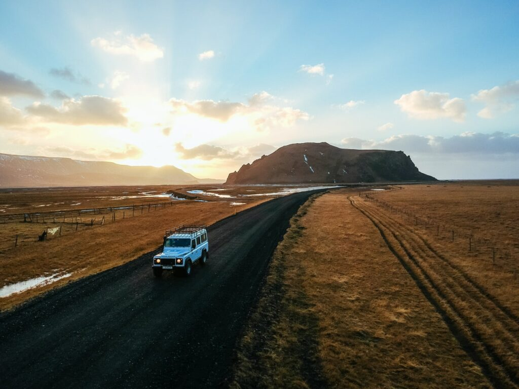 white jeep driving in a sunset in Iceland